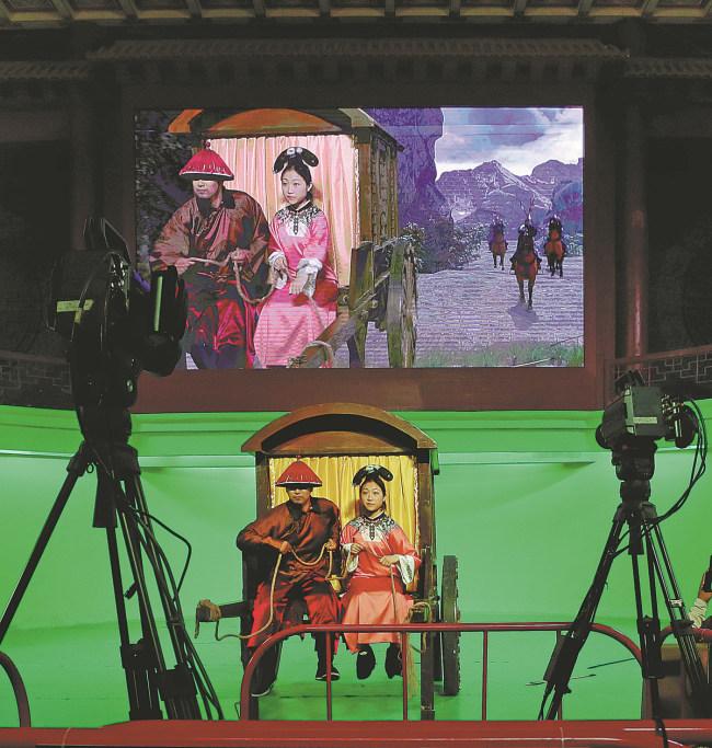 Ένας επισκέπτης (δεξιά), φορώντας ένα κοστούμι από τη δυναστεία Τσινγκ (1644-1911), βιώνει μια στιγμή δράσης στα σκηνικά των κήπων των ανακτόρων δυναστείας Μινγκ και Τσινγκ, στις 18 Ιουλίου. [φωτογραφία / CHINA DAILY]